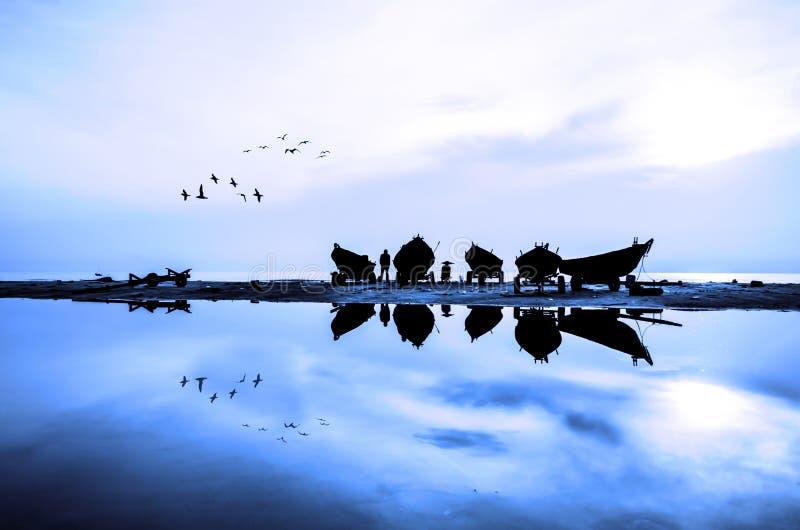 Fartyg på stranden när solresning royaltyfri foto