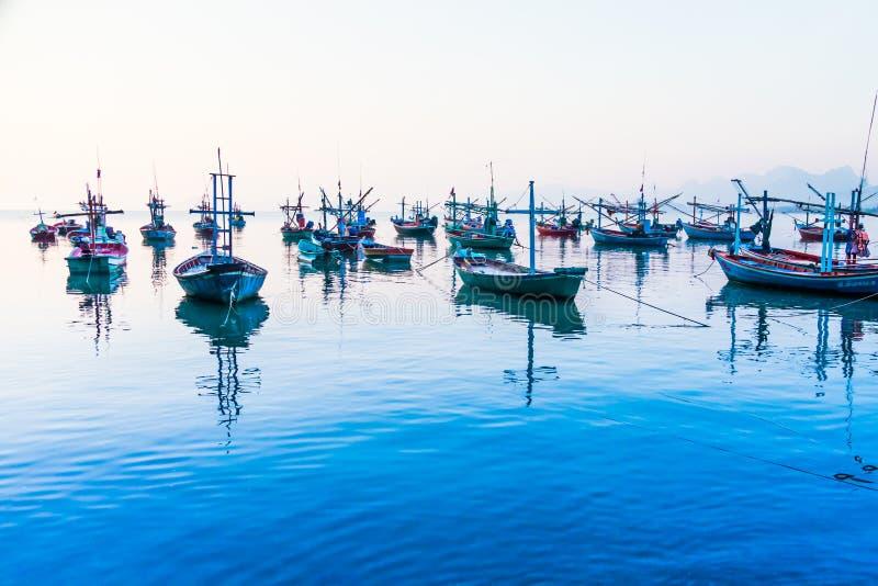 Fartyg som förtöjas nära kusten på soluppgång royaltyfri bild