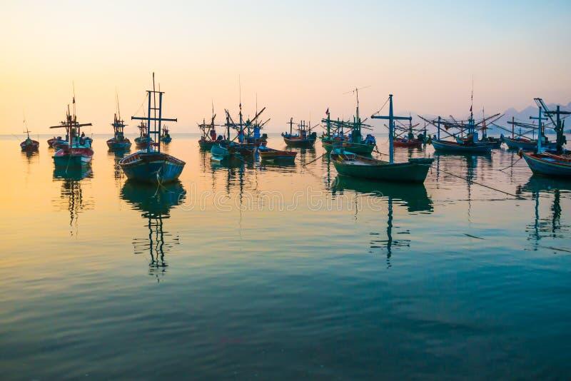 Fartyg som förtöjas nära kusten på soluppgång arkivfoton