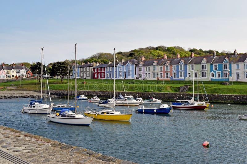 Fartyg som förtöjdes i hamnen med det olikt som ljust färgades, färgade hus i bakgrunden i Wales royaltyfri fotografi