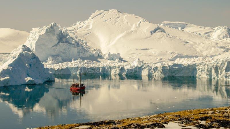 Fartyg som kryssar omkring mellan isberg i Grönland arkivfoton