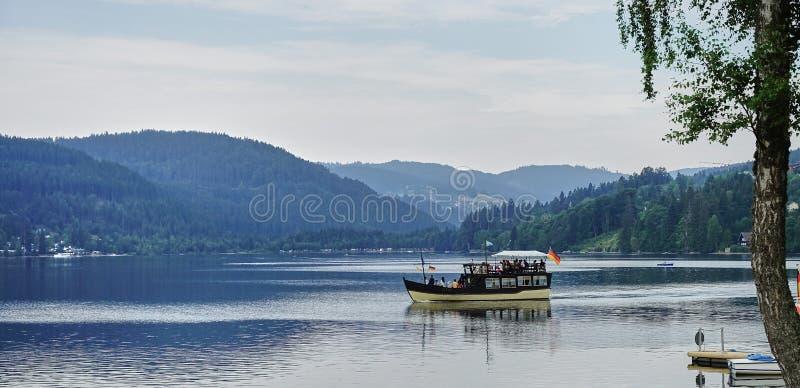 Fartyg som kryssar omkring på svart skog sjön Titisee - Tyskland arkivbilder