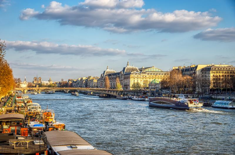 Fartyg trafikerar på Seine River med det Orsay museet i bakgrund - P arkivbild