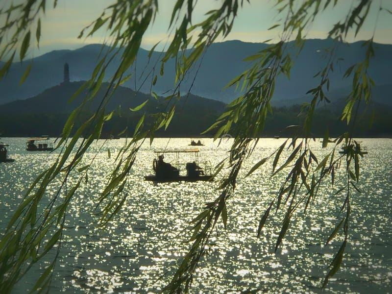Fartygen i den kunming sjön och det yuquan berget i avståndet royaltyfri bild