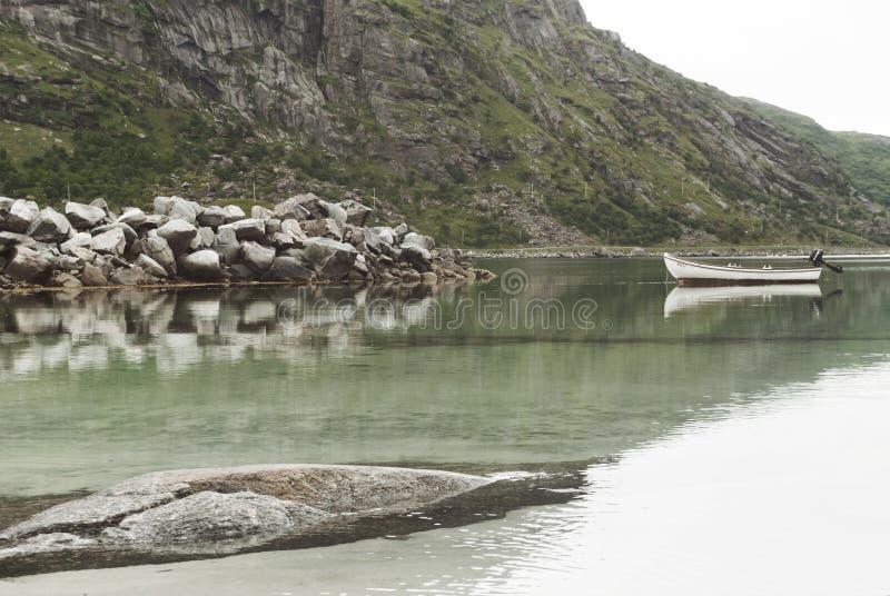 Fartyget och det pittoreskt vaggar reflekteras i klart vatten, Lofoten, Norge royaltyfri foto