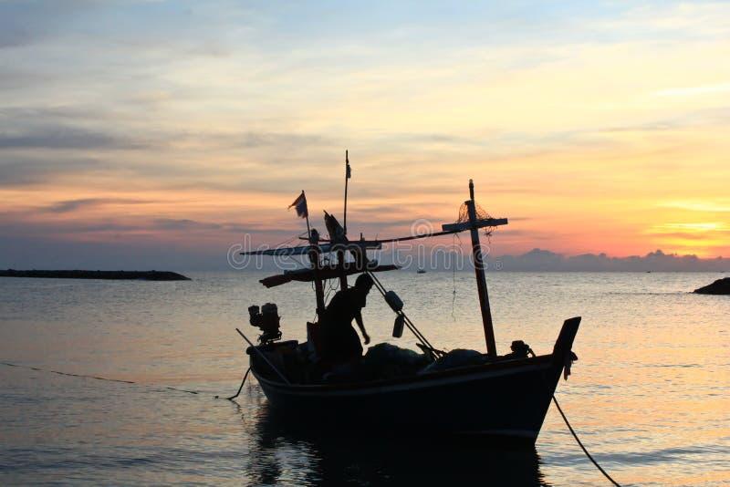 fartygfiskare som fiskar en havssilhouette arkivbild