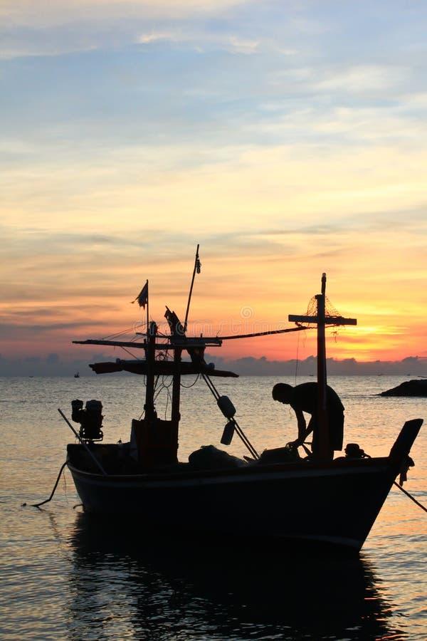 fartygfiskare som fiskar en silhouette arkivfoto