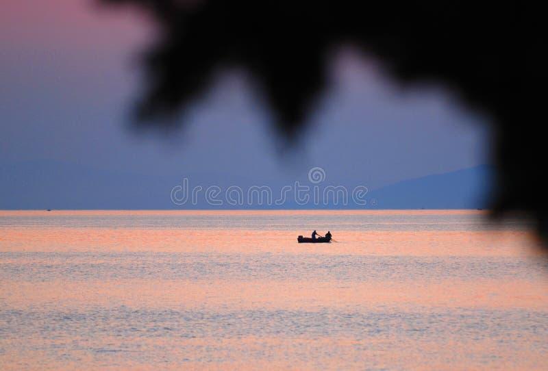 fartygfiskaresolnedgång royaltyfri fotografi