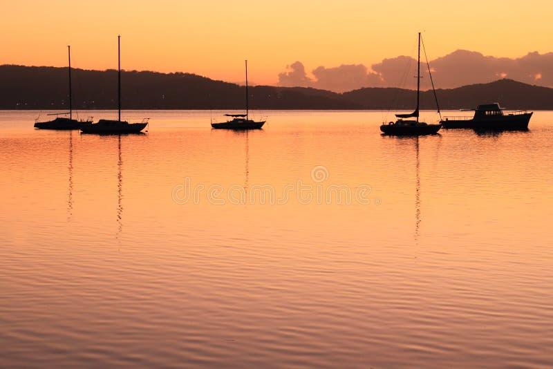 Fartygsilhouettes på laken på gryning royaltyfria foton