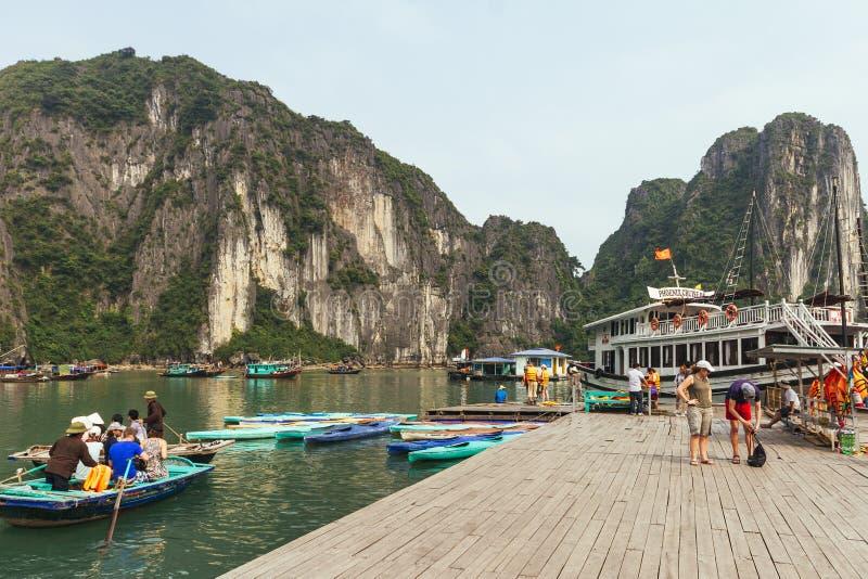 Fartygstopp med många turister som väntar på att resa inom kalkstengrottan med kalkstenön i bakgrund i sommar arkivbilder