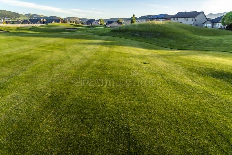 Farwater i bunkiery pole golfowe z w odległości domami i górą obrazy stock