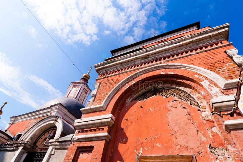 Fasad av den gamla kyrkan för röd tegelsten med guld- kupoler arkivbild