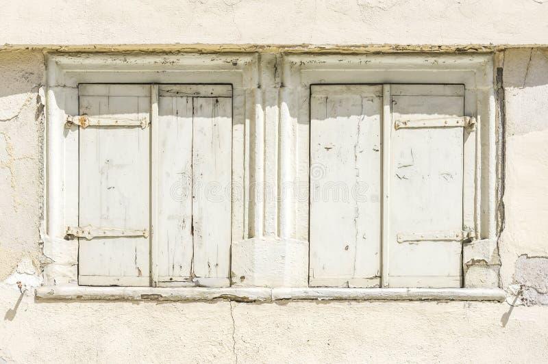 Fasad av det övergav förfallna huset med 2 fönster med shutt royaltyfria foton