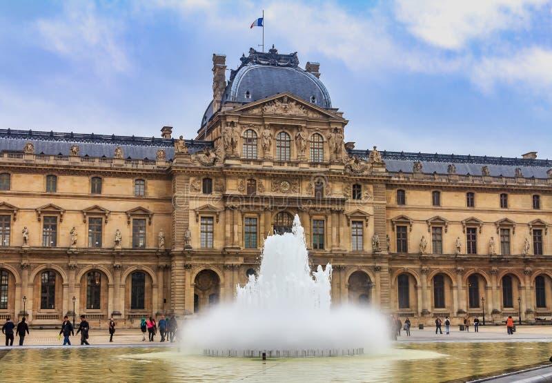 Fasad av det berömda Louvremuseet, en av världens största konstmusem och en historisk monument med en springbrunn framme in arkivbilder