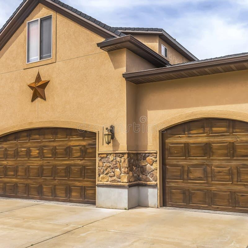 Fasad av det härliga huset med två bruna trägaragedörrar mot molnig himmel arkivfoto
