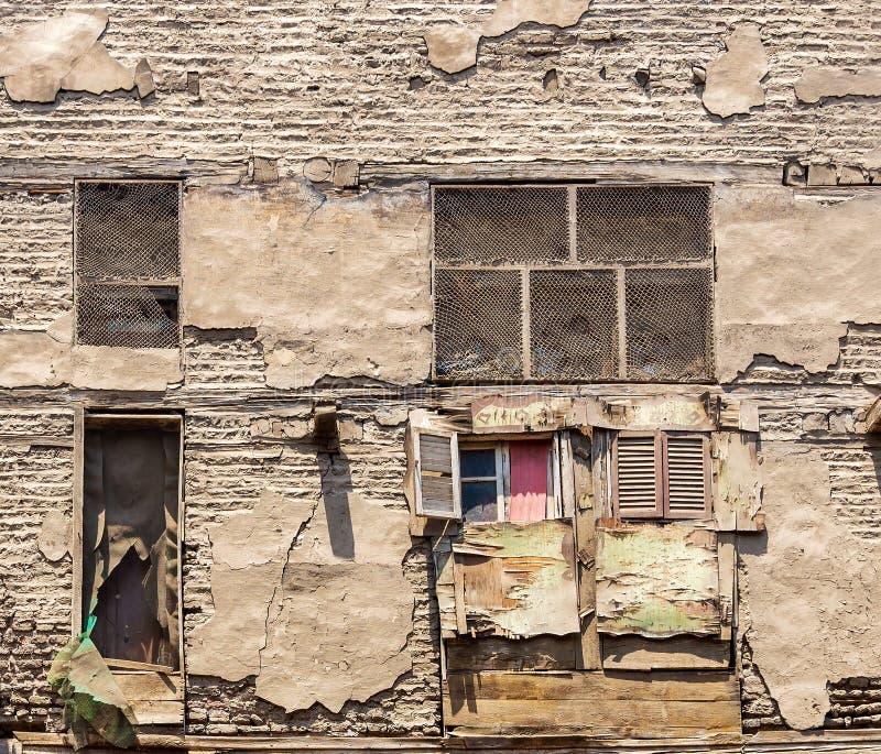 Fasad av en gammal övergiven byggnad med väggen för grungestentegelstenar och spridda träfönster med brutna slutare arkivfoto