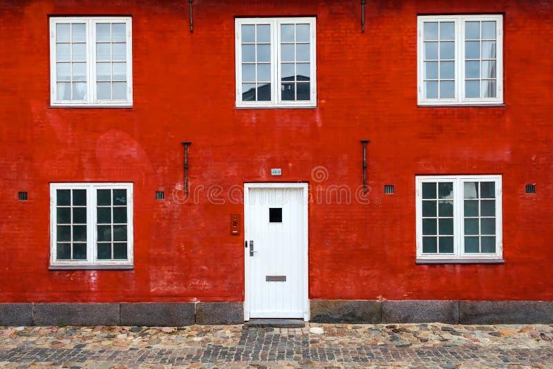 Fasad av en gammal byggnad med ett fönster och en ingångsdörr mot en röd tegelsten arkivfoton