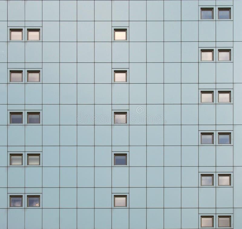 Fasad av en modern byggnad med geometrisk metallisk cladding och att upprepa modellfönster royaltyfri fotografi