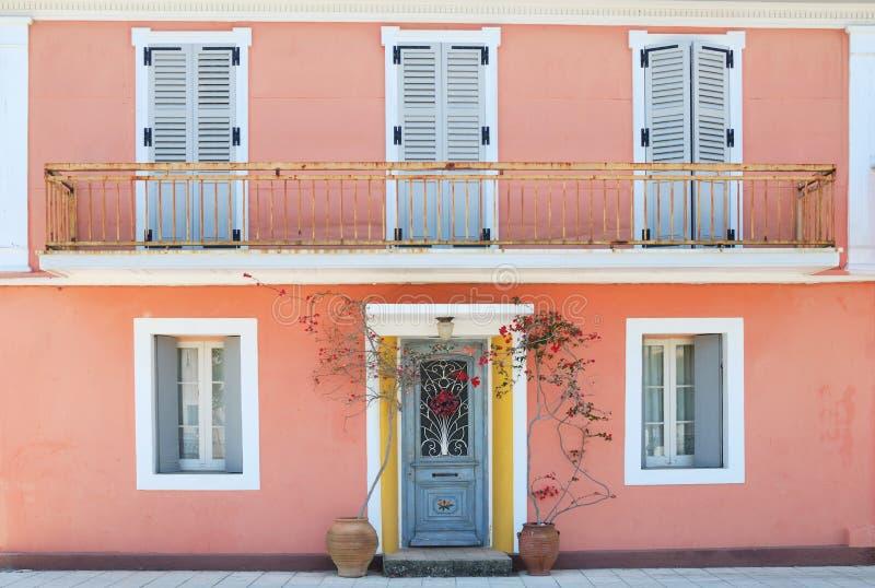 Fasad av ett älskvärt grekiskt hus med blommor och balkongen arkivfoto