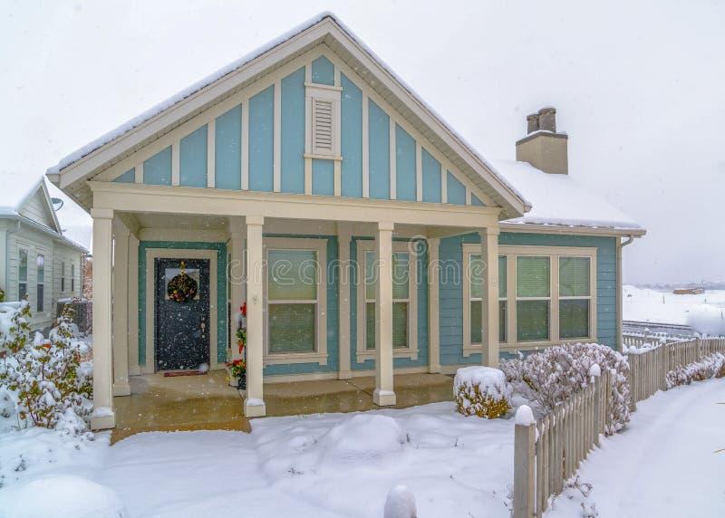 Fasad av ett blått hem som beskådas på en snöig vinterdag royaltyfria bilder
