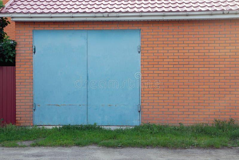 Fasad av ett brunt tegelstengarage med blåa metallportar royaltyfri foto