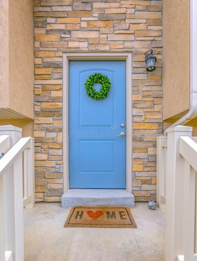 Fasad av ett hem med den blåa ytterdörren och lampan på stentegelstenväggen arkivfoton