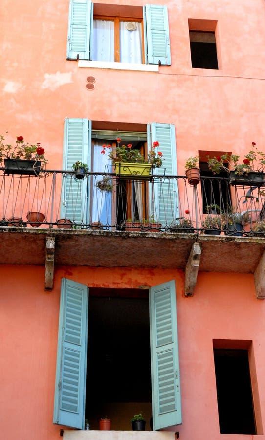Fasad av ett hus, med två fönster och en glass dörr till Verona arkivfoton