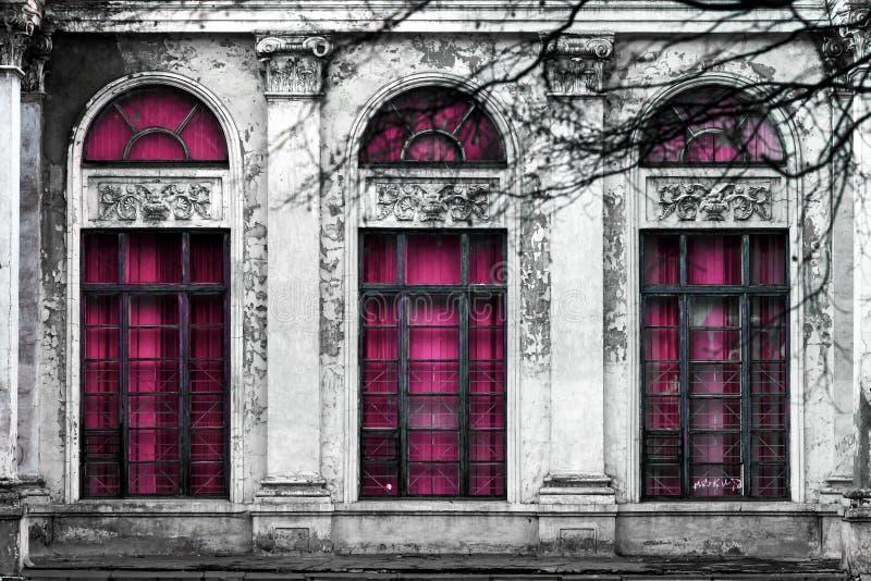 Fasad av gammal övergiven byggnad med tre stora välvda fönster av rosa exponeringsglas Monokrom bakgrund arkivfoto