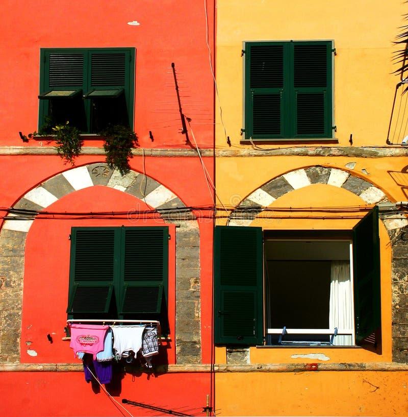 Fasad av röda och gula byggnader med grönt fönster fyra royaltyfri bild