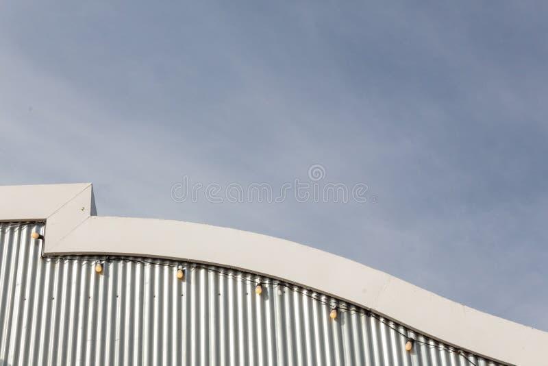 Fasad med den korrugerade metallsidingen och ljus, klara himlar med whispy moln royaltyfri bild