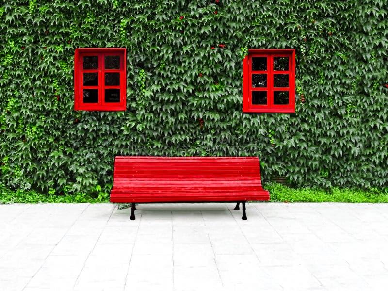 Fasad med gröna trädgårds- och röda fönster för lodlinje i en hållbar byggnad royaltyfria bilder