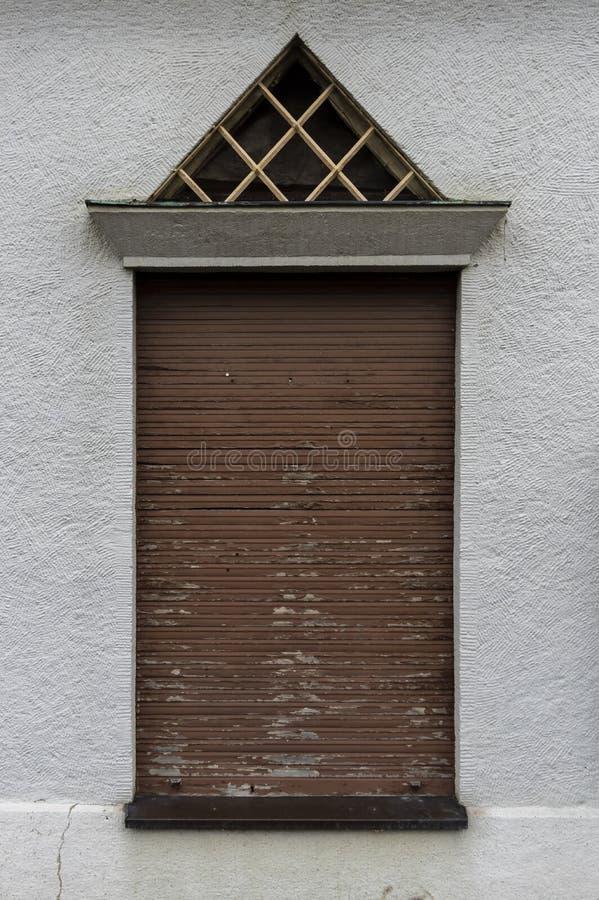 Fasad med höga fönster och stängda gamla träslutare, triangulär takfönster med skyddsgallret som inbrottstjuvskydd och murbruk in arkivfoto