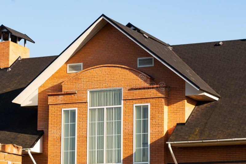 Fasada ceglany dwór z trzy prostokątnymi okno, kominowych i multilevel dachami, zdjęcie stock