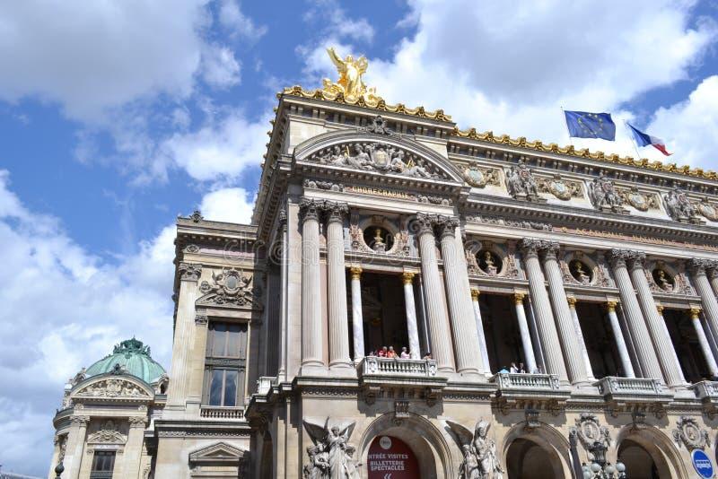 Fasada opera de Paryż z złotymi statuami i flagami na dachu zdjęcie royalty free