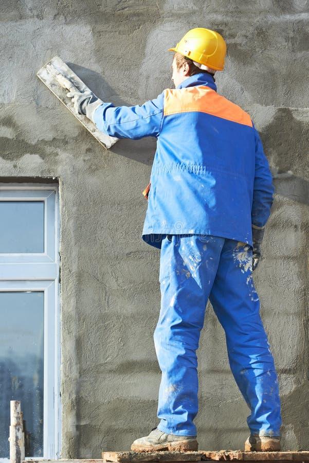 Fasadarbetare som rappar väggen royaltyfria bilder