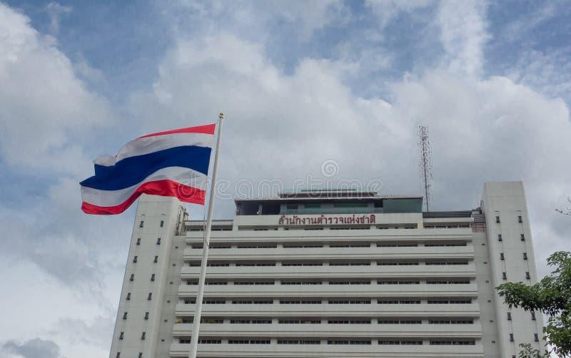 Fasadbyggnaden av kungliga thailändska polishögkvarter med den Thailand flaggan framme av den med molnig dag för blå himmel arkivfoto