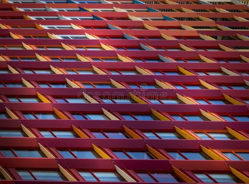 Fasadbyggnadssikt av färgade fönsterramar arkivbild