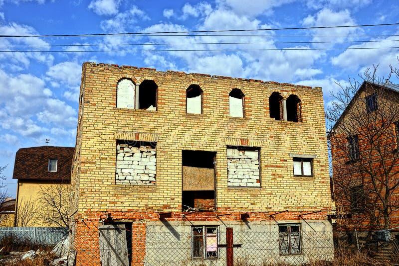 Fasaden av det förstörda tegelstenhuset arkivbild