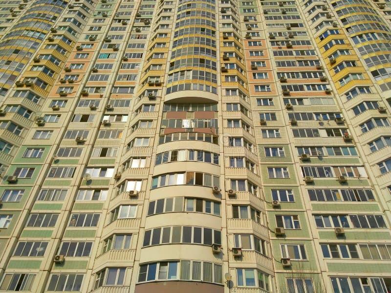 Fasaden av en enorm bostads- byggnad med många fönster och balkonger royaltyfri fotografi