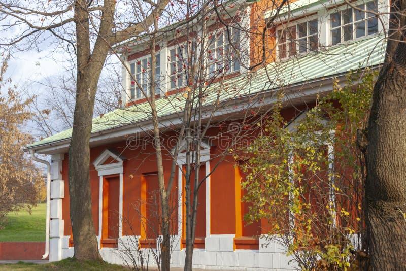 Fasaden av en gammal byggnad två-berättelse för röd tegelsten med ett vitt tak i hösten parkerar arkivbilder