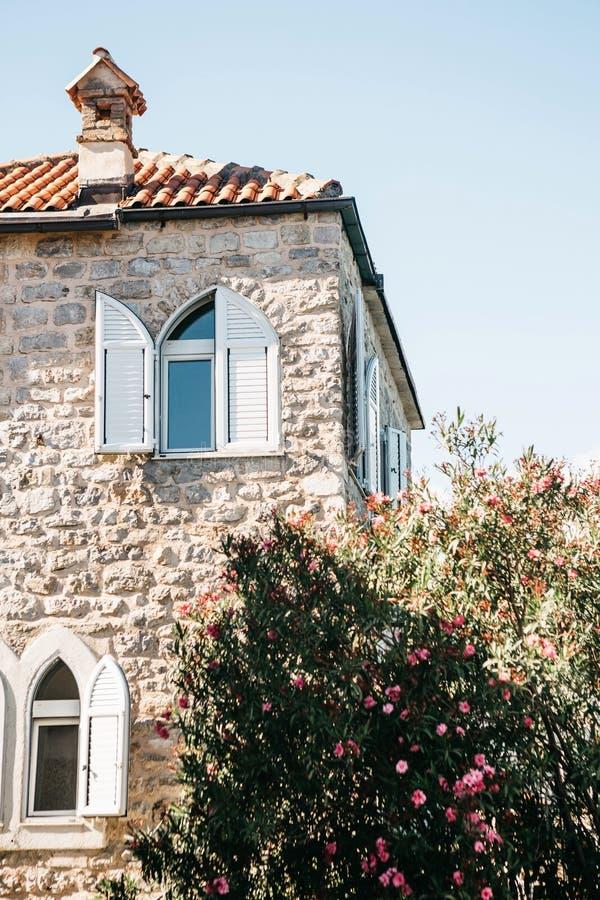 Fasaden av en vanlig gammal byggnad med fönster i Montenegro royaltyfri fotografi