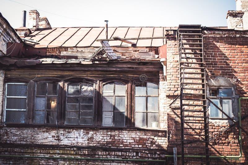 Fasaden av ett gammalt tegelstenhus med ett fragment av taket och lampglasen arkivbilder