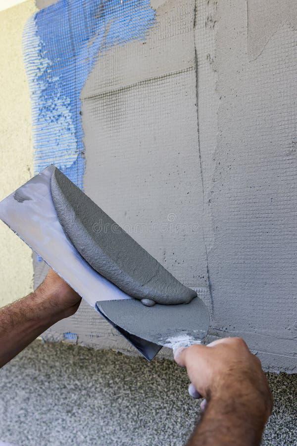 Fasadmurbrukhand som ut slätar väggen med murslev 2 fotografering för bildbyråer