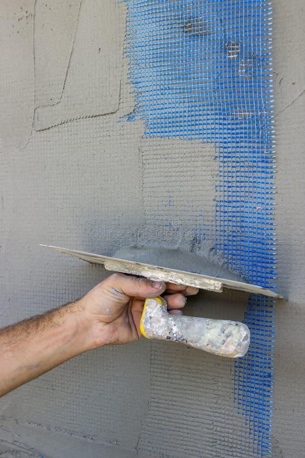 Fasadmurbrukhand som ut slätar väggen med mursleven royaltyfri foto