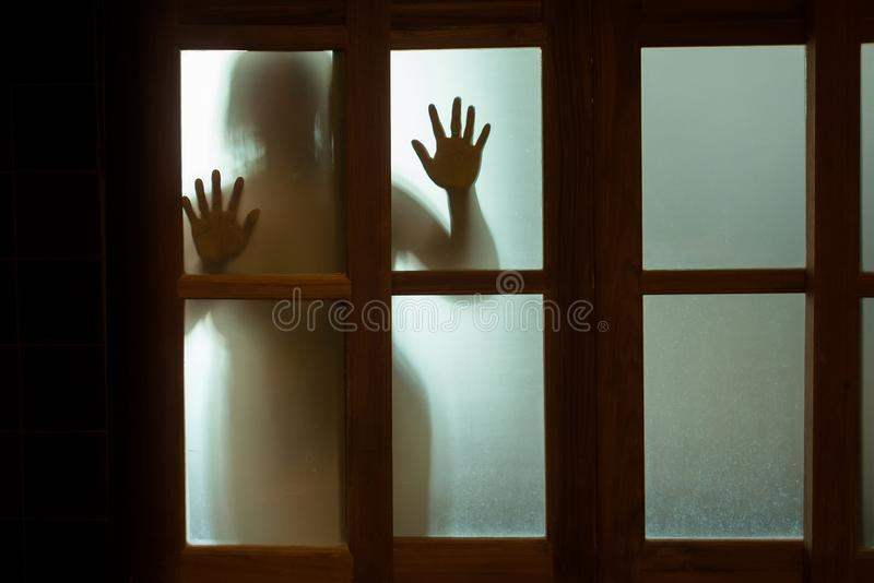 Fasakvinna bak fönsterexponeringsglaset i svartvitt oskarpa arkivbild