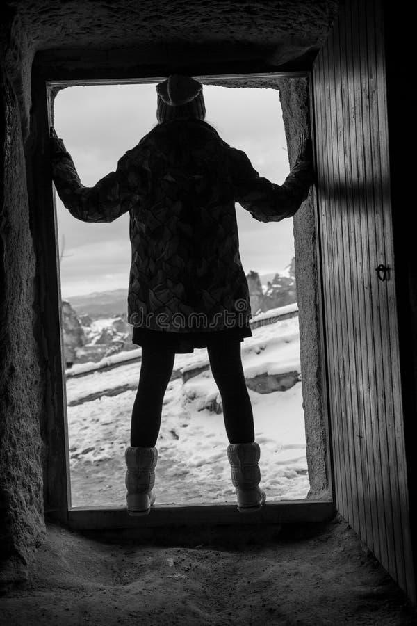 Fasaplats av en kvinna som är besatt med det oskarpa Head innehavet en docka på ytterdörren av ett gammalt hus royaltyfri foto