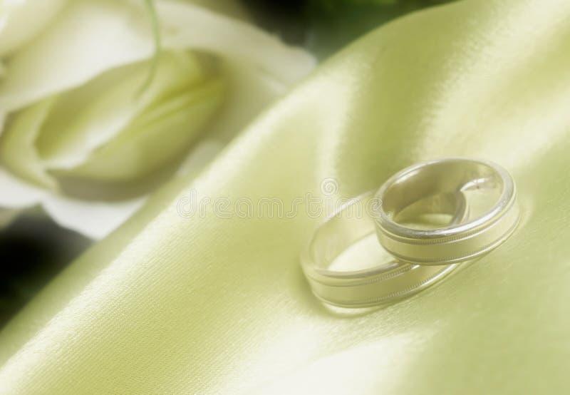 Fasce di cerimonia nuziale su raso verde in vago immagini stock