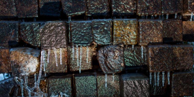 Fasci di legno coperti di ghiaccio e ghiaccioli fotografia stock libera da diritti