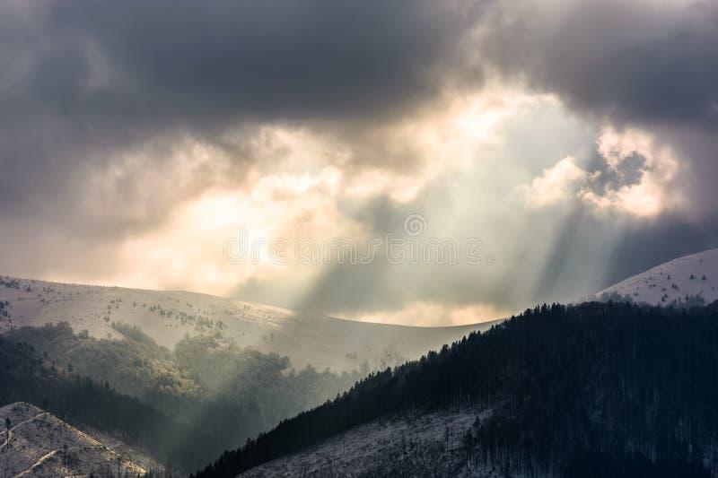 Fasci luminosi sopra le montagne immagine stock