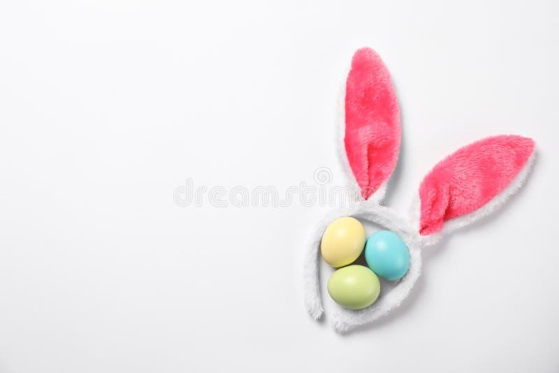 Fascia divertente con le orecchie del coniglietto di pasqua ed il fondo bianco tinto delle uova fotografie stock